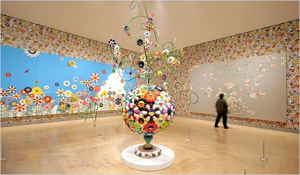 """[Photo: Julien Jourdes for The New York Times] From left to right, Kawaii-Vacances (2002), Flower Matango (2001-2006) and Cosmos (1998) One example is the riot of manically cheerful flowers created by the combination of wallpaper, paintings and one sculpture in a large gallery. The blooms look like petal-ringed smiley faces, only better — and crazier. The ensemble fulfills almost too completely Mr. Murakami's stated desire to make art """"that makes your mind go blank, that leaves you gaping."""""""
