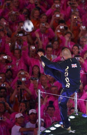 [Photograph: Phil Noble/Reuters] David Beckham kicks a ball into the crowd during the closing ceremony